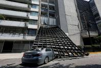 A damaged car is seen outside a building after an earthquake in Mexico City