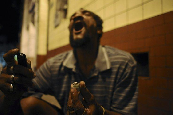 """A drug user consumes crack in the old center of Salvador da Bahia March 19, 2012. Many Brazilian cities now have their own """"cracklands,"""" areas of the city where swarms of crack users have converted entire neighborhoods into nocturnal encampments doubling"""