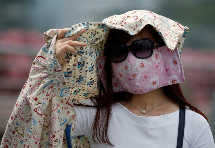 A woman wearing a face mask shields her face from the sun as haze shrouds Singapore