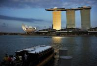 Visitors board a traditional bumboat vessel as sunlight shines on the Marina Bay Sands integrated resort during dusk in downtown Singapore