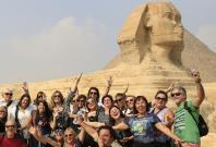 Tourists smile and cheer as they take a souvenir photo in front of the Sphinx at the Giza Pyramids