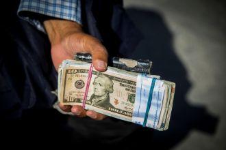 Money changer holds U.S. dollar bills at Grand Bazaar in the center of Tehran