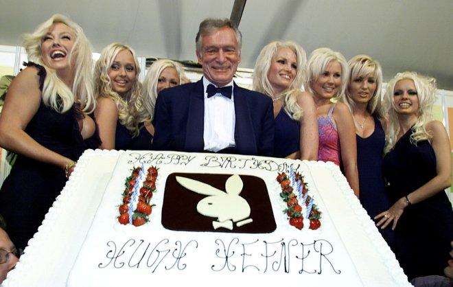 Hugh Hefner (C) Playboy founder and Editor-in-Chief, displays a giant birthday cake