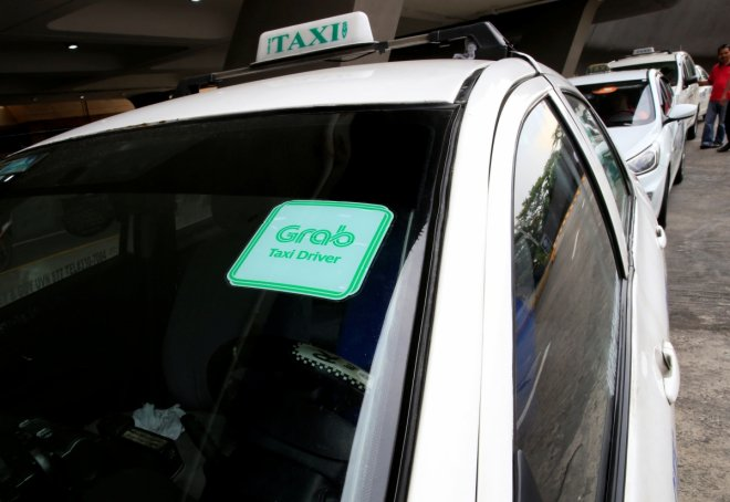 Grab taxi queues while waiting for passengers at the Ninoy Aquino International Airport (NAIA) in the metro Manila, Philippines, July 22, 2016. This logo has been updated and is no longer in use.