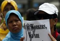 Domestic helpers rally in support of an Indonesian maid who was tortured by her employers