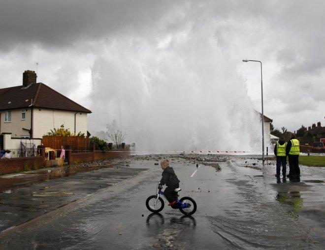 A boy cycles through a puddle as a burst main shoots a plume of water into the air in the Huyton area of Liverpool, northern England, July 18, 2011. The burst main led to localized flooding and evacuations of residents. REUTERS/Phil Noble (BRITAIN - Tags: