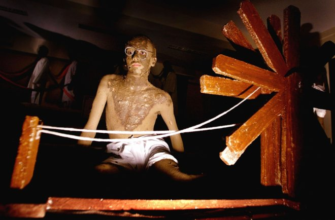 An Indian college student, smeared with clay to resemble Mahatma Gandhi, sits beside a spinning wheel during an event to mark the 55th anniversary of the death of Gandhi in Bombay January 30, 2003. Students from a city college reenacted several scenes fro