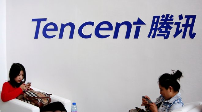 Visitors use their smartphones underneath the logo of Tencent at the Global Mobile Internet Conference in Beijing May 6, 2014. REUTERS/Kim Kyung-Hoon/File Photo