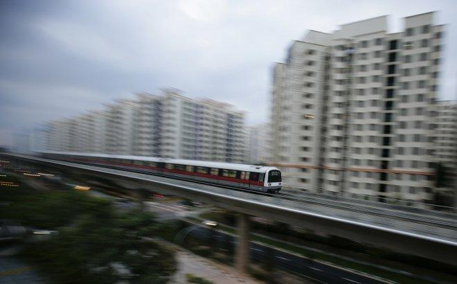 A MRT train travels along a track in a neighbourhood in Singapore