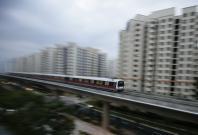A MRT train travels along a track in a neighbourhood in Singapore