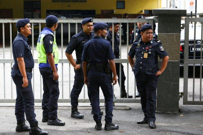 Malaysian police officers gather in front of the gate of the morgue at Kuala Lumpur General Hospital
