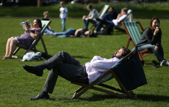 People relax in the sunshine on a warm day in London, Britain May 4, 2016.