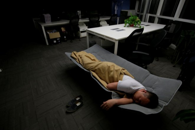 Ma Zhenguo, a system engineer at RenRen Credit Management Co., sleeps on a camp bed at the office after finishing work early morning, in Beijing, China, April 27, 2016. Office workers sleeping on the job is a common sight in China, where a surplus of chea