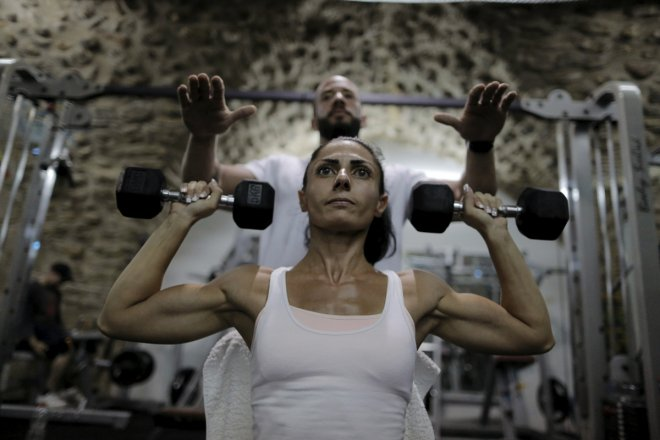 Palestinian bodybuilder Anoush Belian trains with her coach Basil Saed in a gym in Jerusalem's Old City August 20, 2015. Belian on Saturday became the first Palestinian female bodybuilder to participate and win an Israeli competition. Belian won the Miss