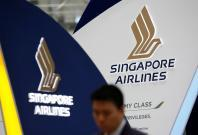 A man walks past a Singapore Airlines signage at Changi Airport in Singapore