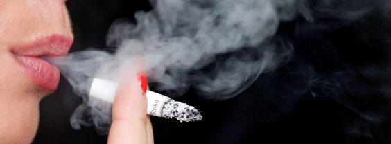 Smoke rises from a burning cigarette as a woman smokes on the street in Bordeaux
