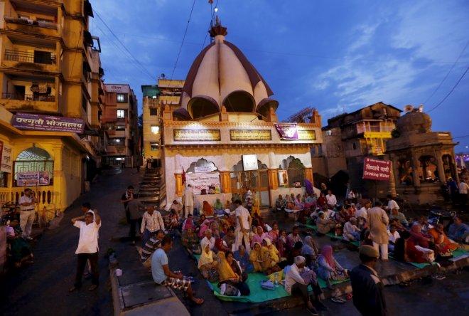 Devotees pray outside a temple on the banks of Godavari river during Kumbh Mela in Nashik, India