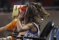A young baseball fan makes sure there's not a kernel of popcorn left as she watches the Chicago Cubs play the Arizona Diamondbacks during their MLB National League baseball game in Phoenix, Arizona, June 24, 2012.