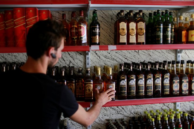 A liquor store owner checks bottles of alcohol at his store in the town of Qaraqosh