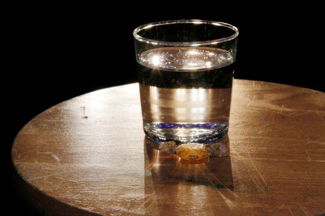 A cough drop and a glass of water are placed on a stool