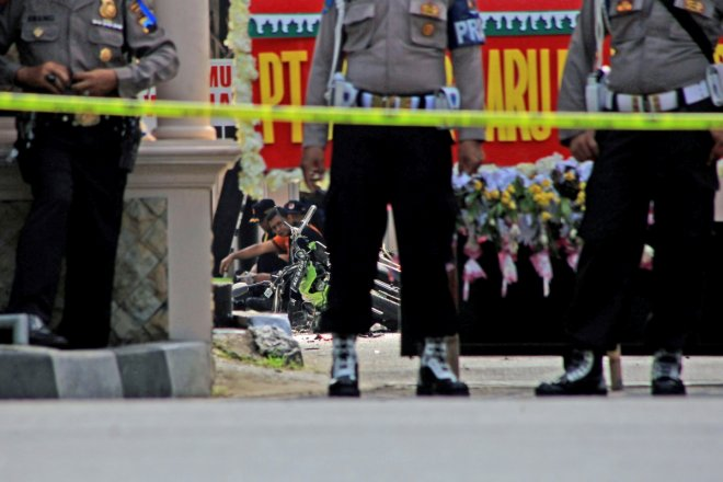 Police secure the scene at a police station following an attack in Solo, Central Java, Indonesia