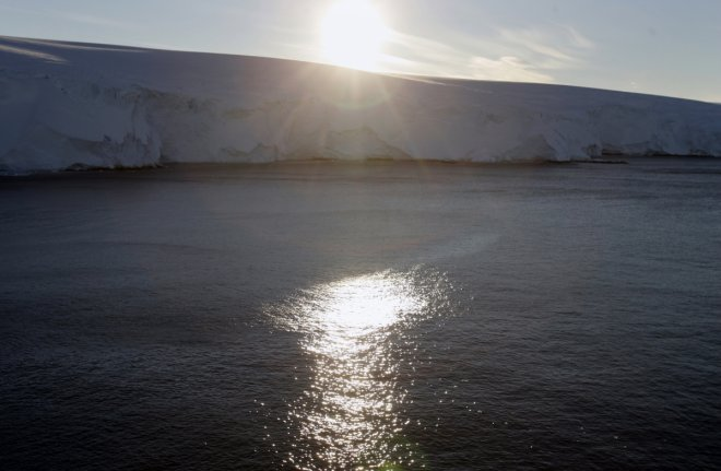 The sun sets behind the coastline at Cape Denison, Commonwealth Bay, East Antarctica