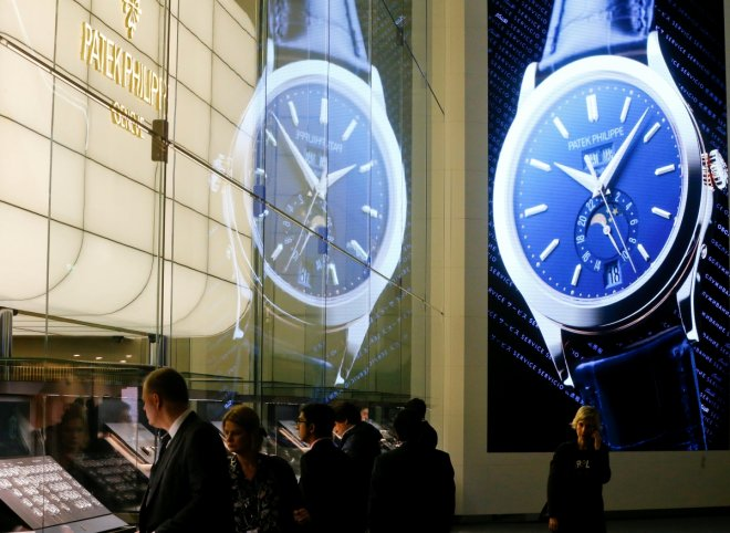 Visitors stand in front of the exhibition stand of Swiss watch manufacturer Patek Philippe
