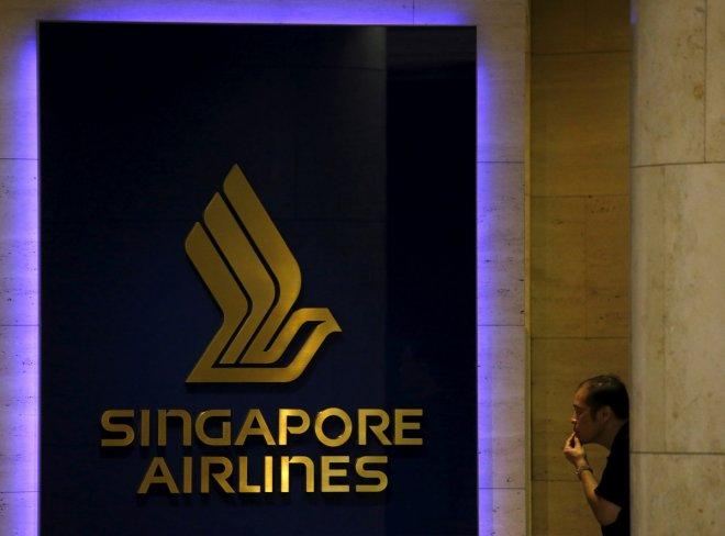 FILE PHOTO: A man looks at a Singapore Airlines (SIA) signage outside an SIA service center in Singapore February 10, 2016.