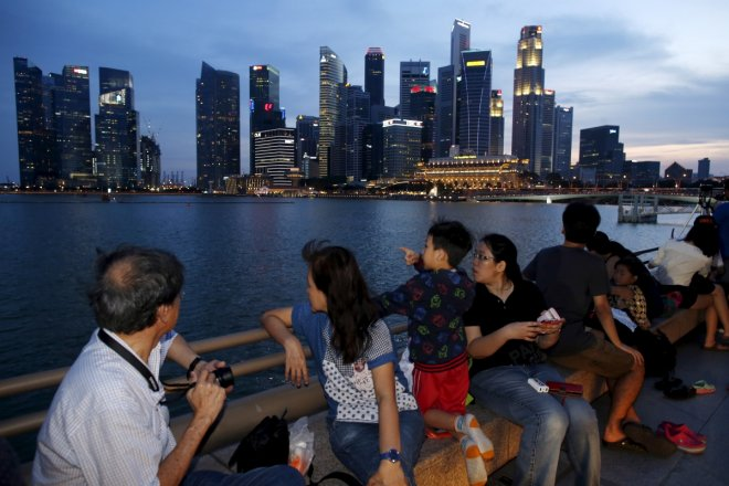 People wait for fireworks during a Golden Jubilee National Day Parade rehearsal along the Marina Bay