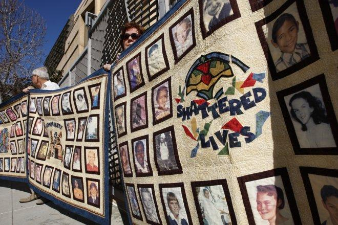 People hold quilts at a press conference outside of Cathedral of Our Lady of the Angels for victims of sexual abuse