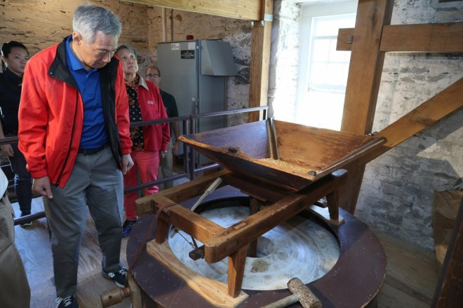 At the historic Peirce Mill. Dried corn drops from the trough in a steady stream into the grindstone to be ground into flour.