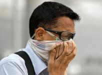 A man covers his face as he walks to work in Delhi