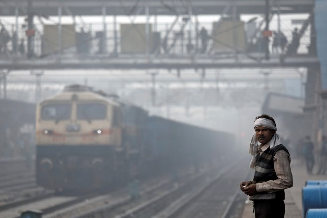 A man stands on railway platform on a smoggy morning in Delhi