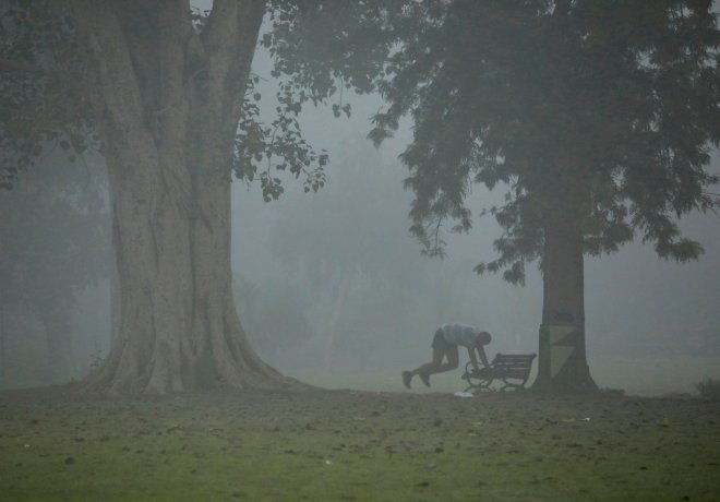 A man exercises in a park on a smoggy morning in New Delhi.