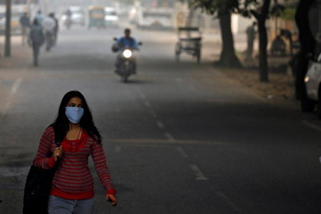 A woman walks along the road on a smoggy morning in Delhi.