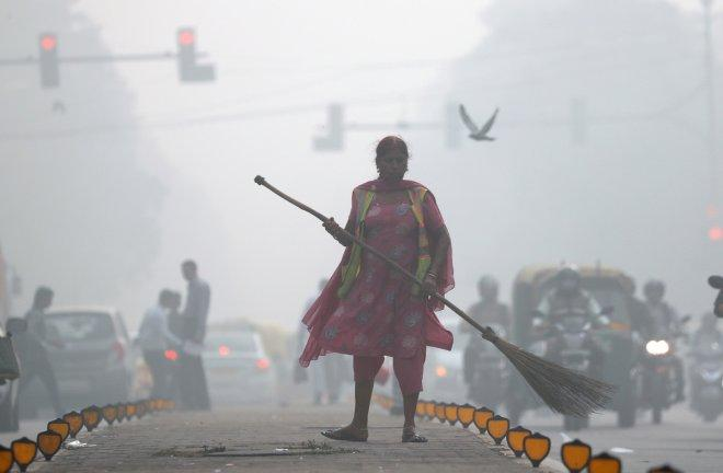 A street cleaner works in heavy smog in Delhi. India plans to use fire trucks to spray water over parts of its capital to combat toxic smog and dust that has triggered a pollution emergency, with conditions expected to worsen over the weekend.