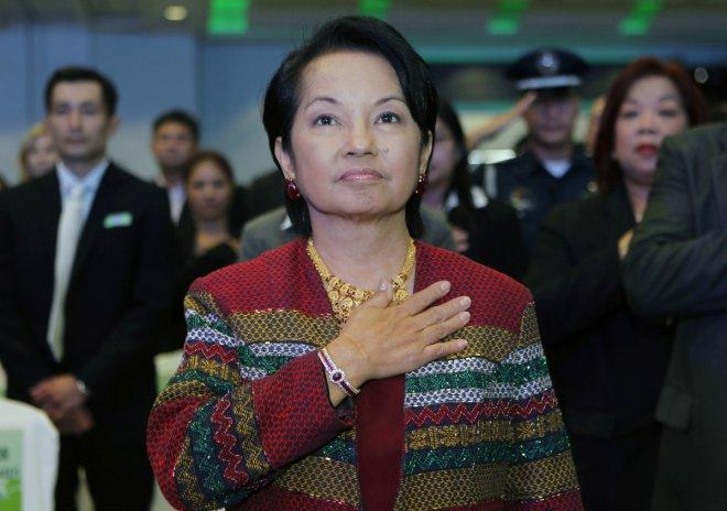 Outgoing Philippine President Gloria Macapagal Arroyo stands on attention