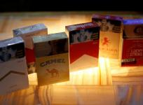 Packs of Marlboro cigarettes, a pack of Camel cigarettes, and a pack of Lucky Strike cigarettes