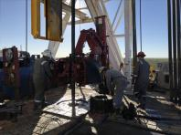 Workers from ScanDrill Ltd clamp together pieces of pipe while drilling an oil well for Jagged Peak Energy Inc near Fort Stockton, Texas.