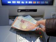 A woman withdraws money from an ATM machine in Nice