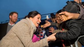 Britain's Prince Harry and his fiancee Meghan Markle greet well wishers as they leave after visiting