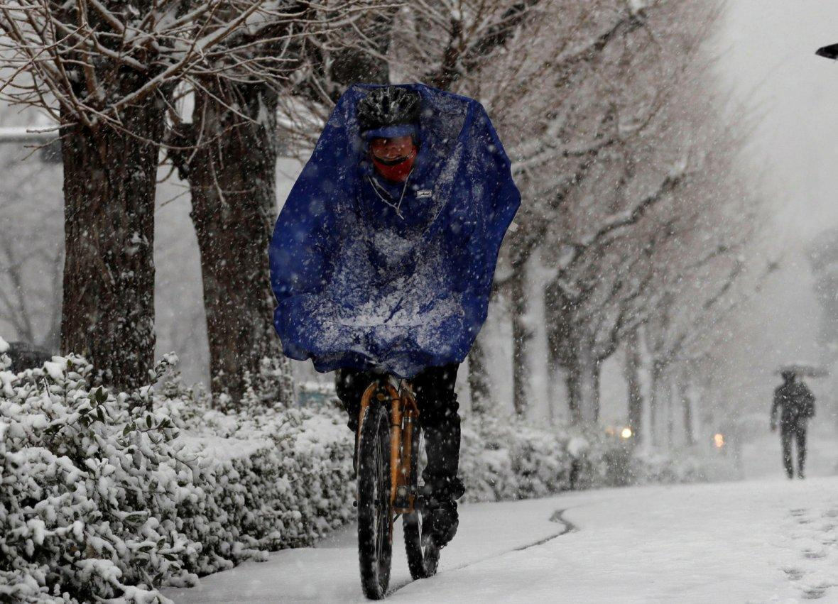 A man rides a bicycle in the heavy snow in Tokyo