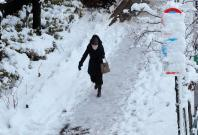 A woman makes her way on a snow-covered sidewalk in Tokyo, Japan, January 23, 2018. REUTERS/Kim Kyung-Hoon