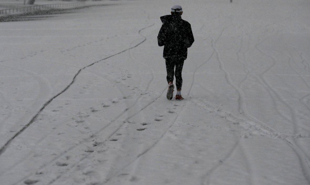 A man jogs in the heavy snow at the Imperial Palace in Tokyo