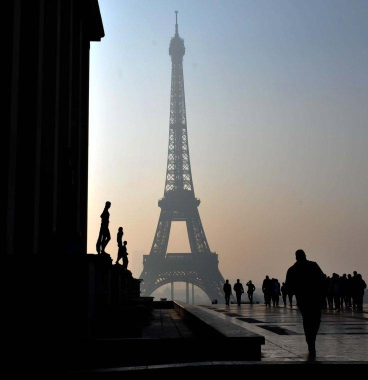 People walk near the Eiffel tower in haze in Paris, capital of France