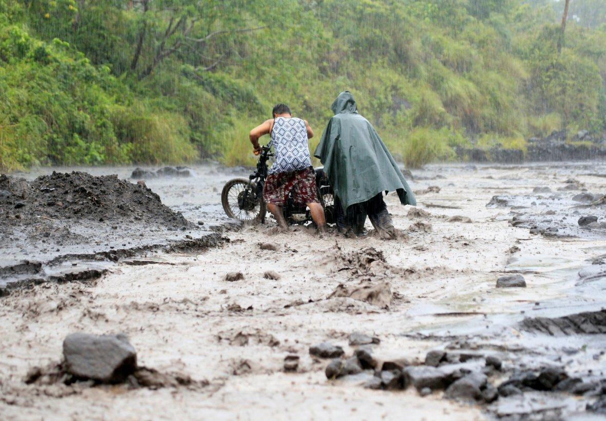 Residents push a motorcycle across a river mixed with lahar from Mount Mayon volcano in Daraga