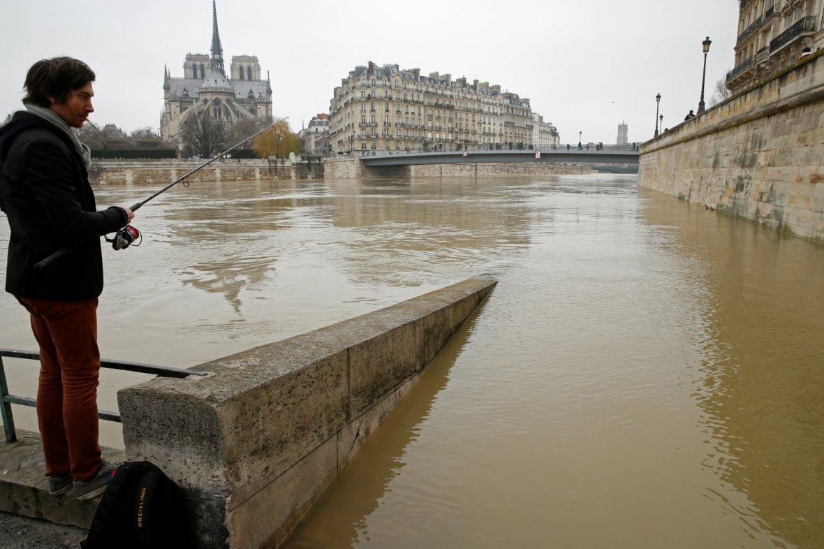 man fishes on the flooded banks of the River Seine in Paris