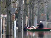 Residents on a small boat leave home in a flooded street of Villeneuve-Saint-Georges