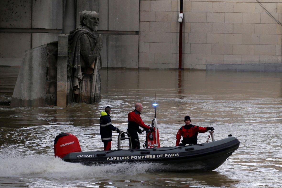 Paris fire brigade navigate a small craft past the Zouave soldier statue under the Pont d'Alma