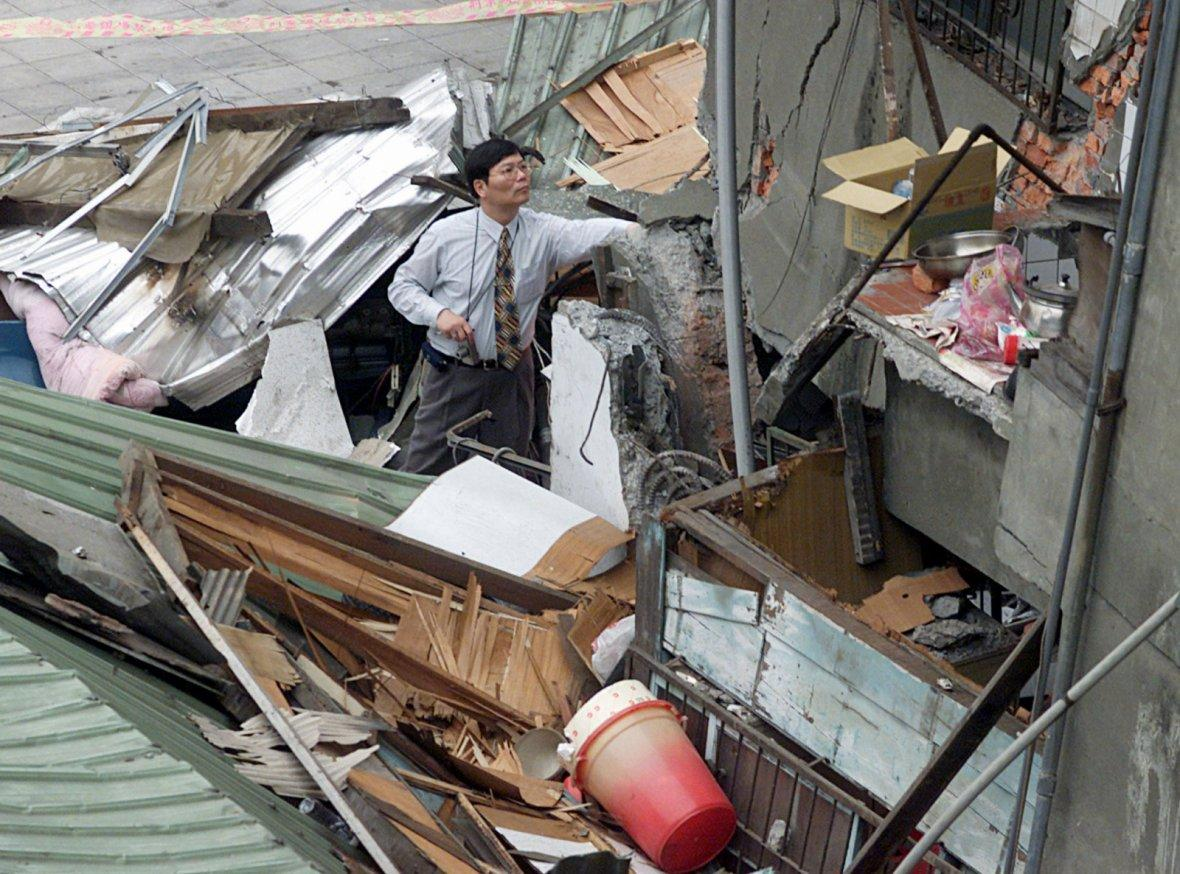 Construction engineer inspects a collapsed building in Taipe.